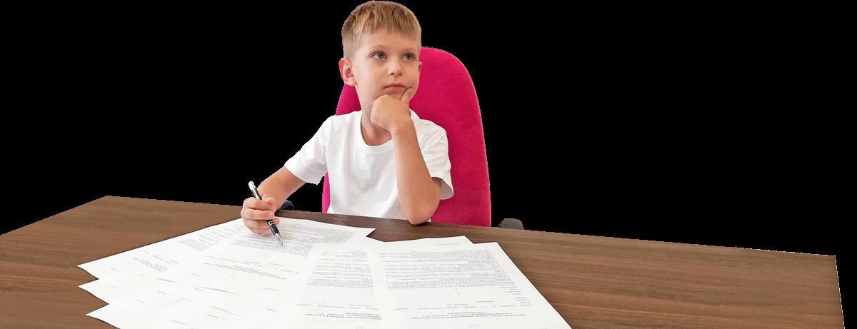 zamyślony chłopczyk przy biurku